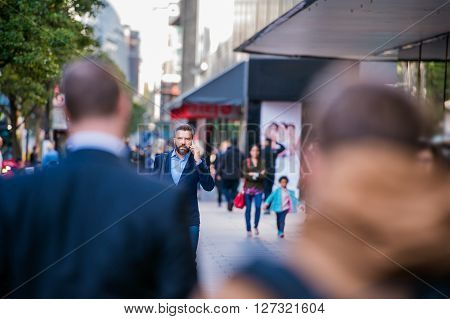 Hipster manager holding a smart phone, making a phone call, walking in the street of London