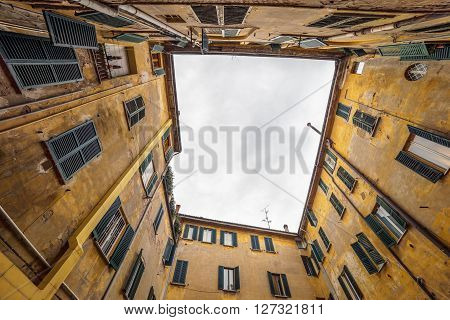 Square courtyard of yellow italian building, bottom view, Ferrara, Italy