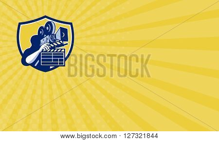 Business card showing illustration of a cameraman movie director holding vintage movie film camera and clapboard set inside shield crest on isolated background done in retro style.