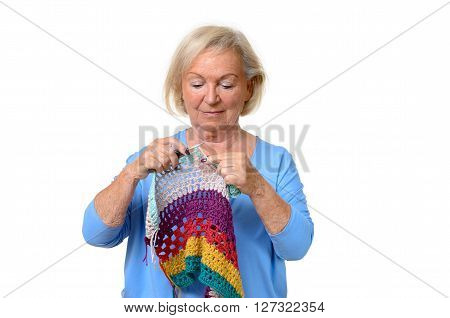 Attractive blond senior lady doing her knitting or crochet work holding a colorful garment in her hands with a look of concentration upper body isolated on white