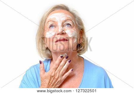 Attractive Senior Woman Applying Cream To Her Skin