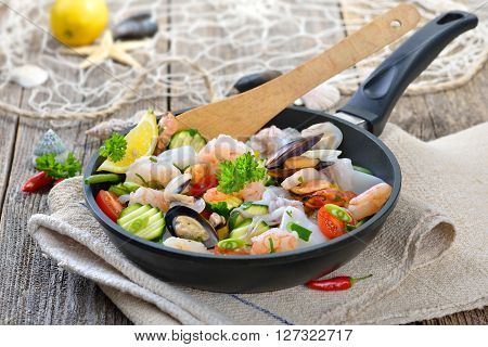 Food combining, mixed seafood and fresh vegetables in a pan before cooking