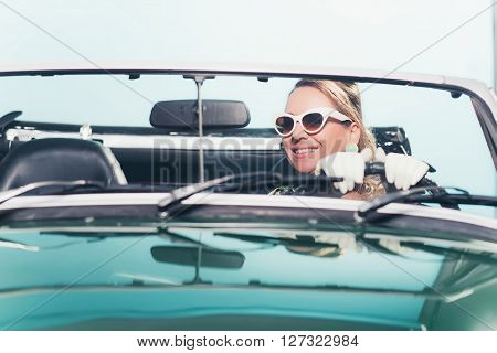 Smiling Retro 1960S Fashion Woman With Shades Driving Convertible.