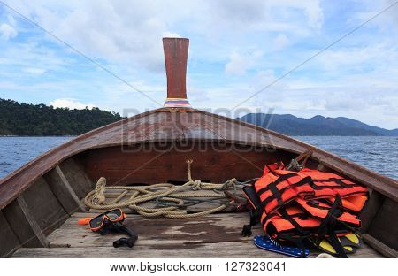 orange snorkel scuba mask and life jackets on nose of long tail boat after a dive