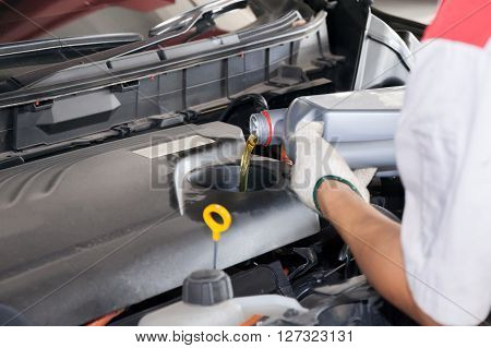 Servicing Mechanic Pouring New Oil Lubricant Into The Car Engine
