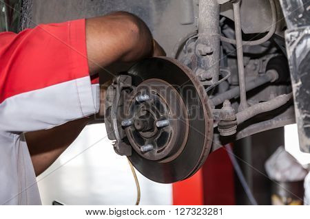 Young Technician Fixing Brake Disk In Car Garage