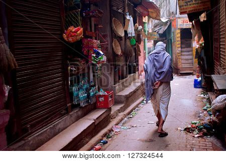 VARANASI, INDIA - JANUARY 3, 2013: Lonely indian senior walk through the narrow streets of the old town with local shops on January 3, 2013 in Varanasi. Approximately 29 perc. of Varanasi's population is employed