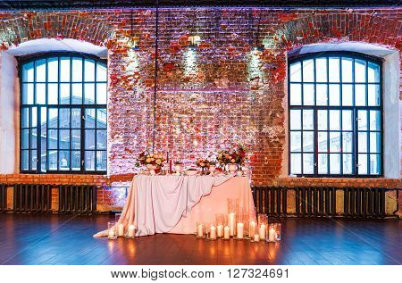 Table set for banquet in loft. Vintage room with brick walls without plaster. Table decorated with candles fabric and flowers.