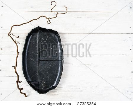 Top view empty black oval plate on rustic wooden table. Ceramic creative black plate on white wooden background with free space. Flat lay of handmade black dish on white wooden table.