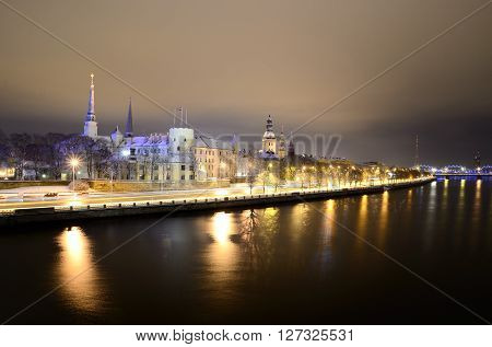 Riga historical city part panorama with night illumination reflecting in Daugava river. Winter Riga landscape.