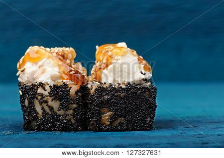 Pair of sushi rolls with cream cheese and caramel sauce in black tobiko roe copyspace closeup