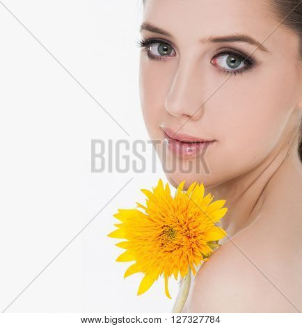 A young woman with a yellow flower, isolated