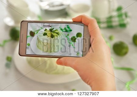 Female hand with smart phone making photo of a creamy lime cake closeup