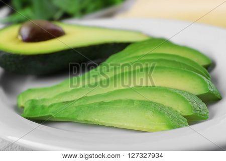 Slices of fresh avocado on plate closeup