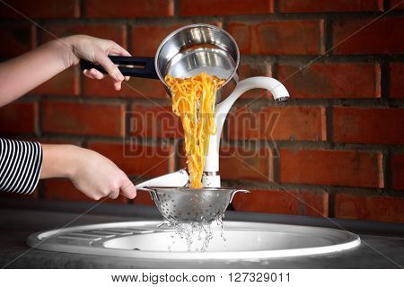 Female hands pouring water from boiled pasta over sink in the kitchen