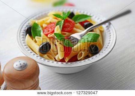 Cooked pasta and fresh tomato impaled on a fork, close up