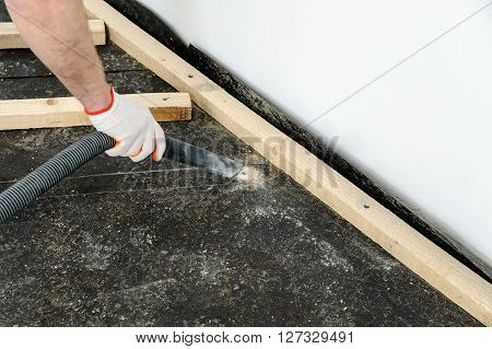 Worker cleans the dust on the floor using a vacuum cleaner.