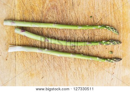 Asparagus spears on a chopping board at right angles to the grain of the board.