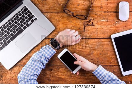 Business person at office desk. Smart watch on hand,  working on smart phone. Notebook, tablet and various office supplies around the workplace. Flat lay.