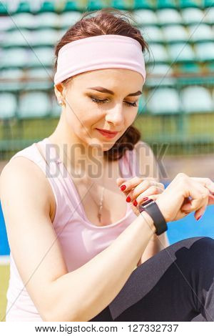 Young Smiling Sporty Woman Using Smartwatch