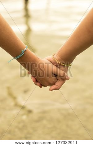 Close Up Of Kids Holding Hands On Beach Concept