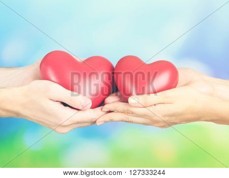 Hearts in hands on nature background. Retro style