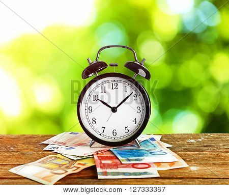 Alarm clock and money on wooden table, green bright background