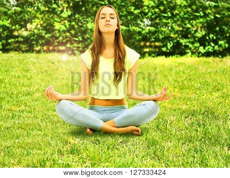 Young beautiful fitness girl doing yoga exercise in park. Retro style
