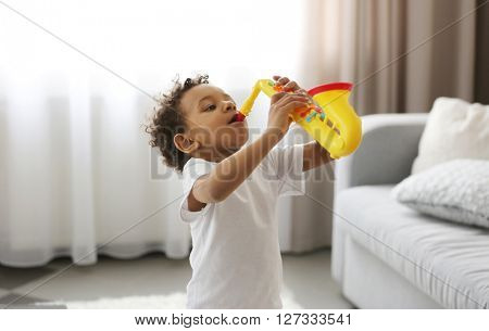 Little boy playing  on toy saxophone