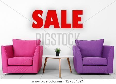 Sale concept. Colorful armchairs, white table and plant near white wall