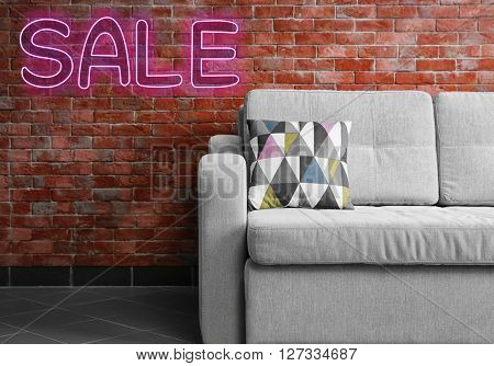 Sale concept. Grey sofa against brick wall in the room