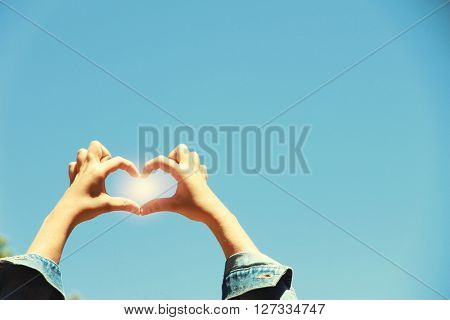 Young girl holding hands on blue sky background. Retro style