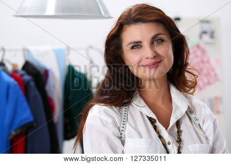 Mature smiling female fashion designer standing in workshop portrait. Style and design development and creating garment, clothes sew and repair service, seamstress at work concept