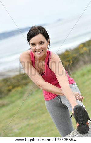 Athletic woman stretching after exercising