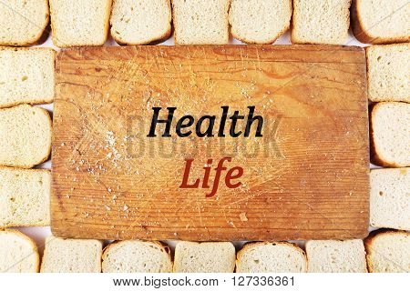 Fresh baked bread slices around cutting board. Health and diet concept