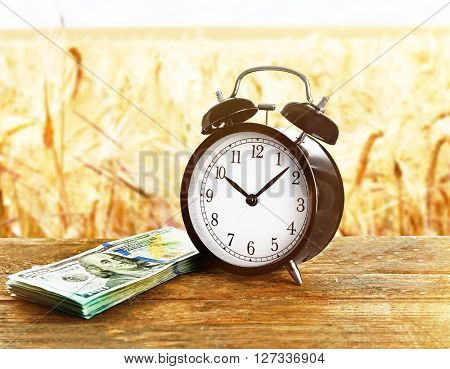 Alarm clock and money on wooden table, wheat field background