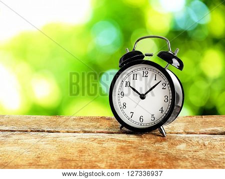 Alarm clock on wooden table on bright background