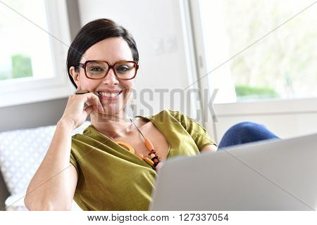 Trendy woman working on laptop from home