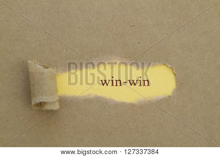 win-win word written under brown torn paper.