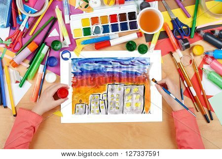 child drawing night city, top view hands with pencil painting picture on paper, artwork workplace