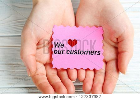 Female hands holding sheet of paper close up, we love our customers