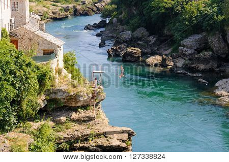 MOSTAR BOSNIA AND HERZEGOVINA - SEPTEMBER 1 2009: Man dives off a platform used for practising and training for higher dives off the Old Bridge