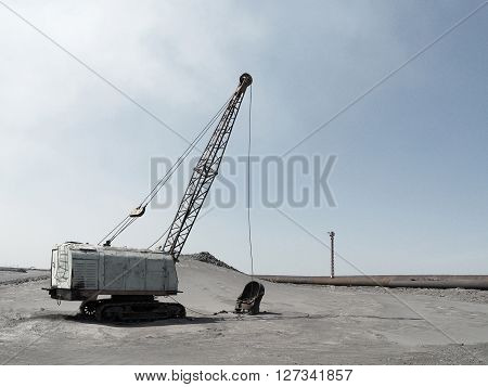 Lone excavator on the field of waste products of metalurgical industry
