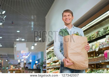 Smiling man with bag indoors