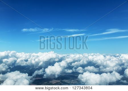 Aerial view of clouds and landscape under them.
