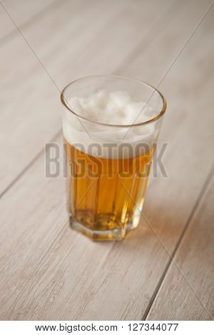 Glass of lager beer on wooden table