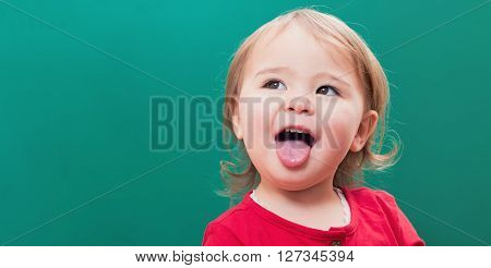 Happy Toddler Girl Sticking Her Tongue Out In Front Of A Chalkboard