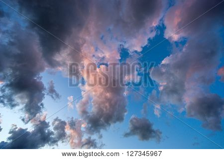 Dramatic cloudscape sky opening showing a hole with bright blue sky
