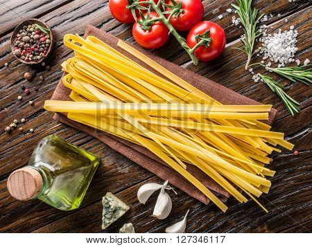 Pasta ingredients. Cherry-tomatoes, spaghetti pasta, rosemary and spices on the wooden table.