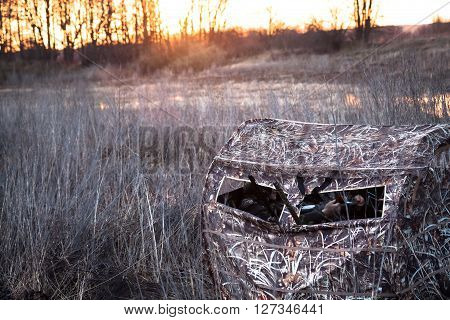 Hunting tent with hunters lurking waiting for prey in the field next to the river while picturesque sunrises